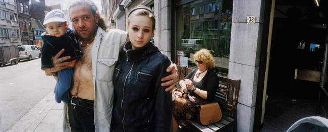 Ein Mann posiert mit einer jungen Frau und einem Baby im Arm vor einem Pub.