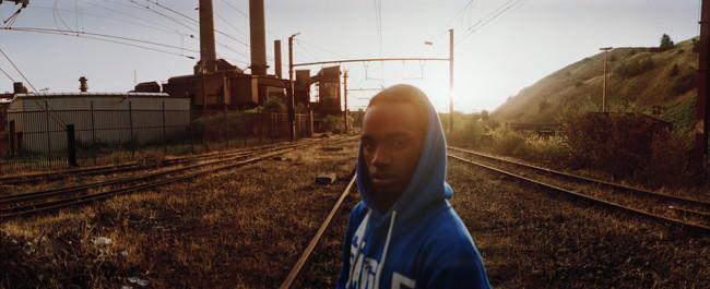 Ein junger Mann im Gegenlicht vor einer Industrielandschaft und überwucherten Gleisen.