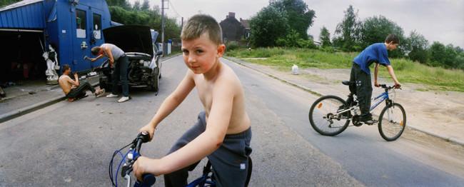 Zwei Jungen auf Fahrrädern, im Hintergrund schrauben zwei Männer an einem Auto.
