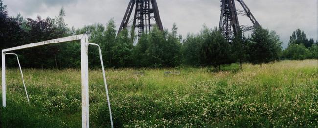 Eine grüne Wiese mit Fußballtor vor einer Industrielandschaft im Hintergrund.