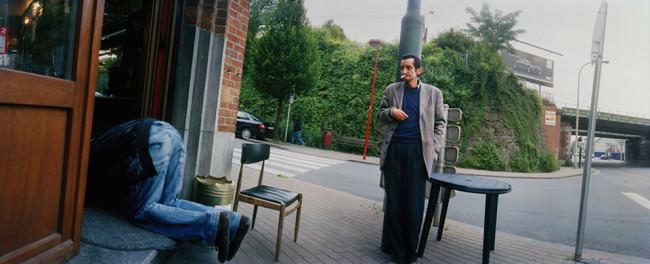 Ein Mann steht vor einer Kneipe und beobachtet einen anderen Mann, der im Eingang auf allen Vieren hockt.