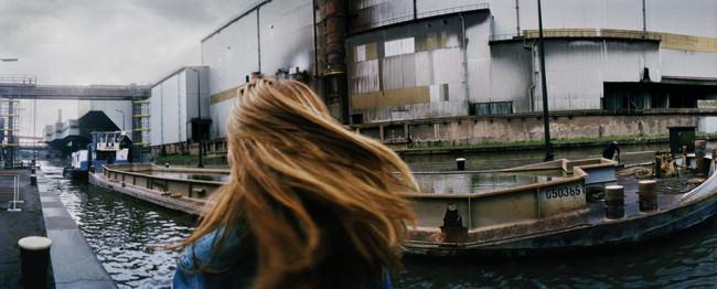 Der fliegende Haarschopf eines Mädchens vor einer Industrielandschaft am Ufer eines Kanals.
