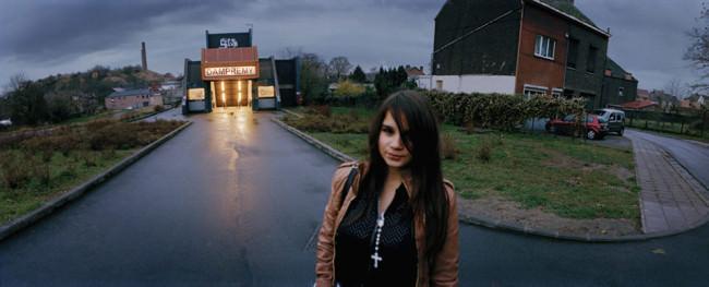 Eine junge Frau vor einem Wohnhaus, neben dem eine Disco hell erleuchtet steht.