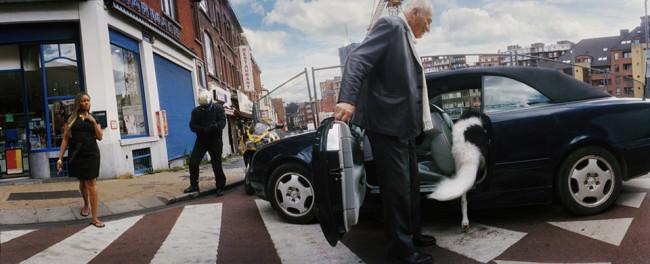Auf einer Straßenkreuzung hält ein Mann die Tür zu einem Auto auf, in dem gerade ein Hund verschwindet.