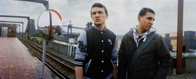 Zwei junge Männer an einer Bahnhaltestelle.