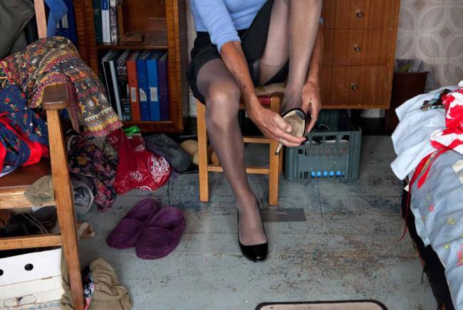 Dianna beim anziehen, sie sitzt auf einem Stuhl und hat eine Strumpfhose an.