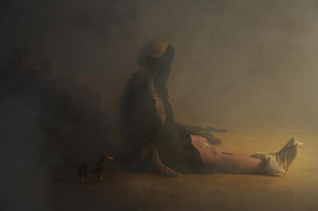 Eine Frau mit langen Zöpfen sitzt auf dem Boden im Nebel.