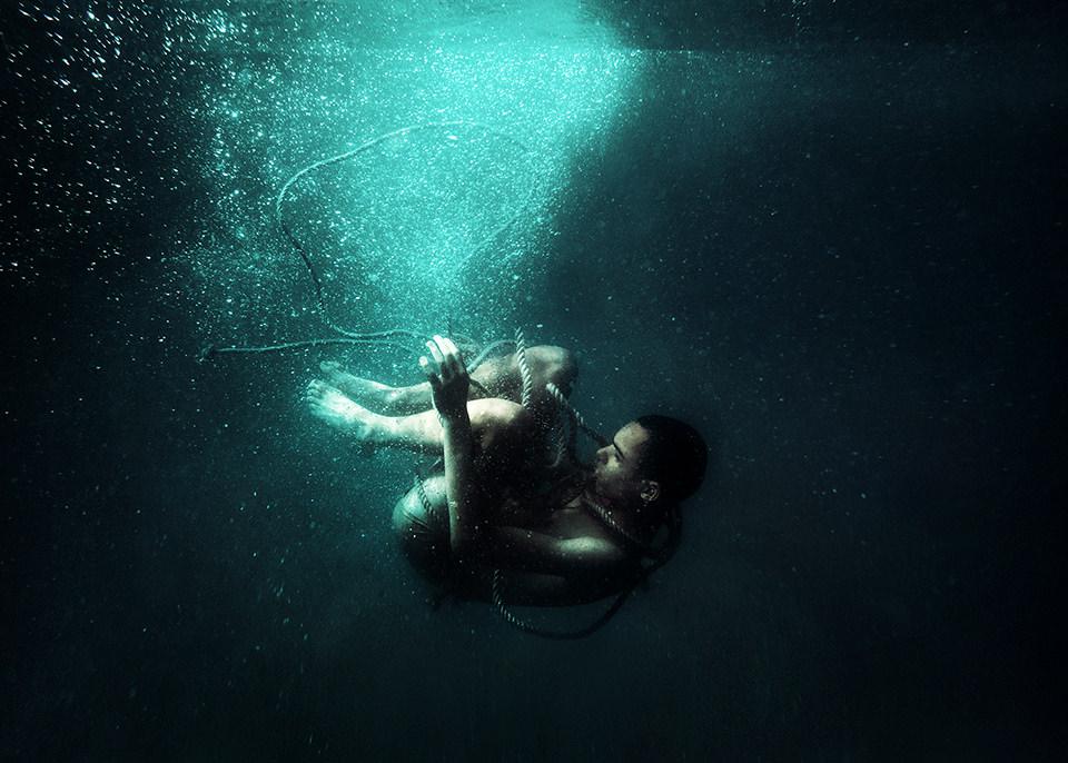Ein Mann mit Seilen gefesselt Unterwasser