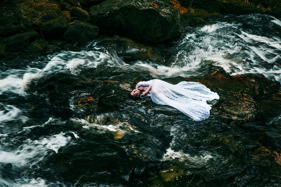 Eine Frau auf einem Stein zwischen stöhmendem Wasser.