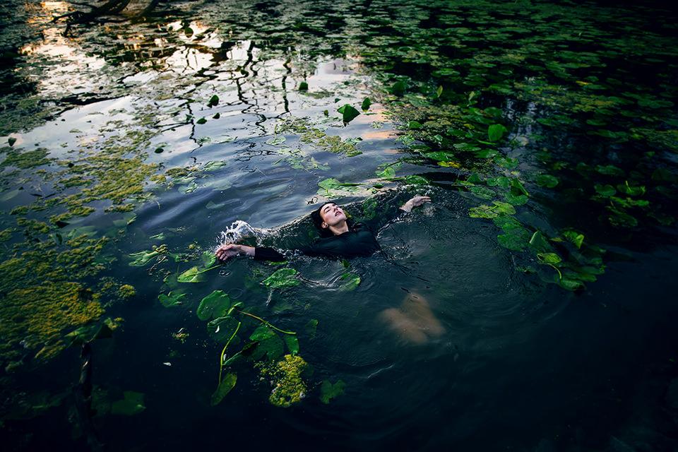 Eine Frau schwimmt zwischen Seerosen.