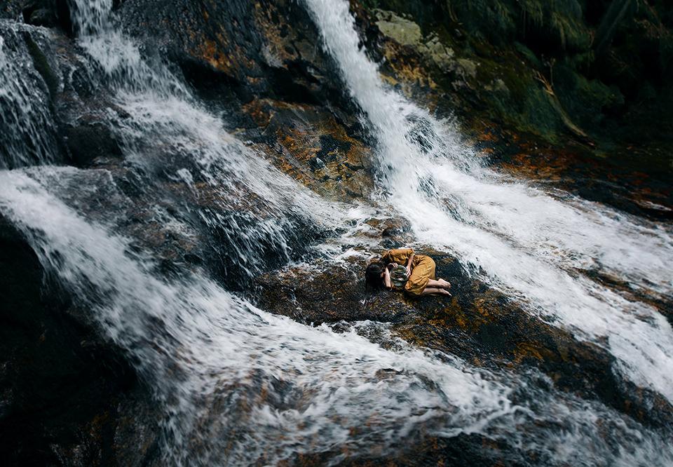 Eine Frau umklammert ein Goldfischglas inmitten eines Wasserfalls.