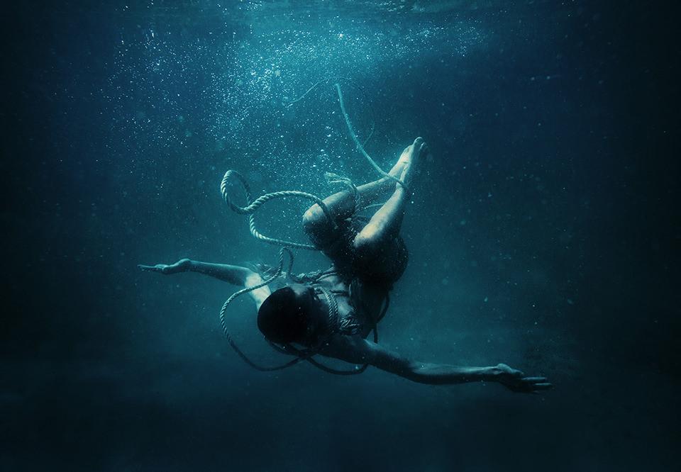 Ein Mann mit Seilen gefesselt Unterwasser.