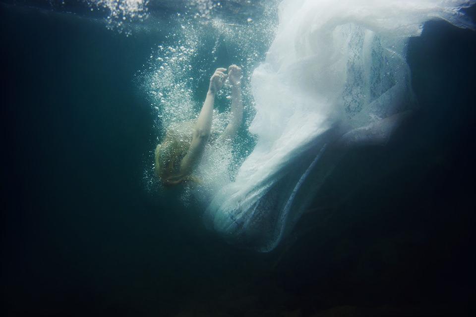 Eine Frau Unterwasser, ist anscheinend gerade hineingefallen und sinkt zum Grund.