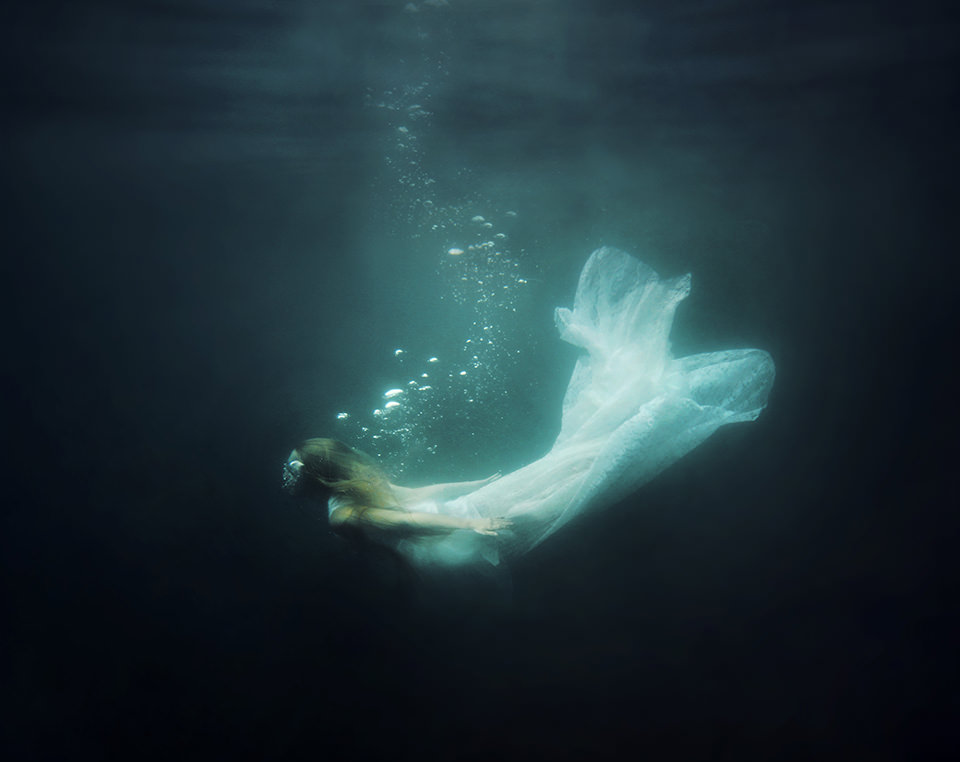 Eine Frau im weißen Kleid Unterwasser.