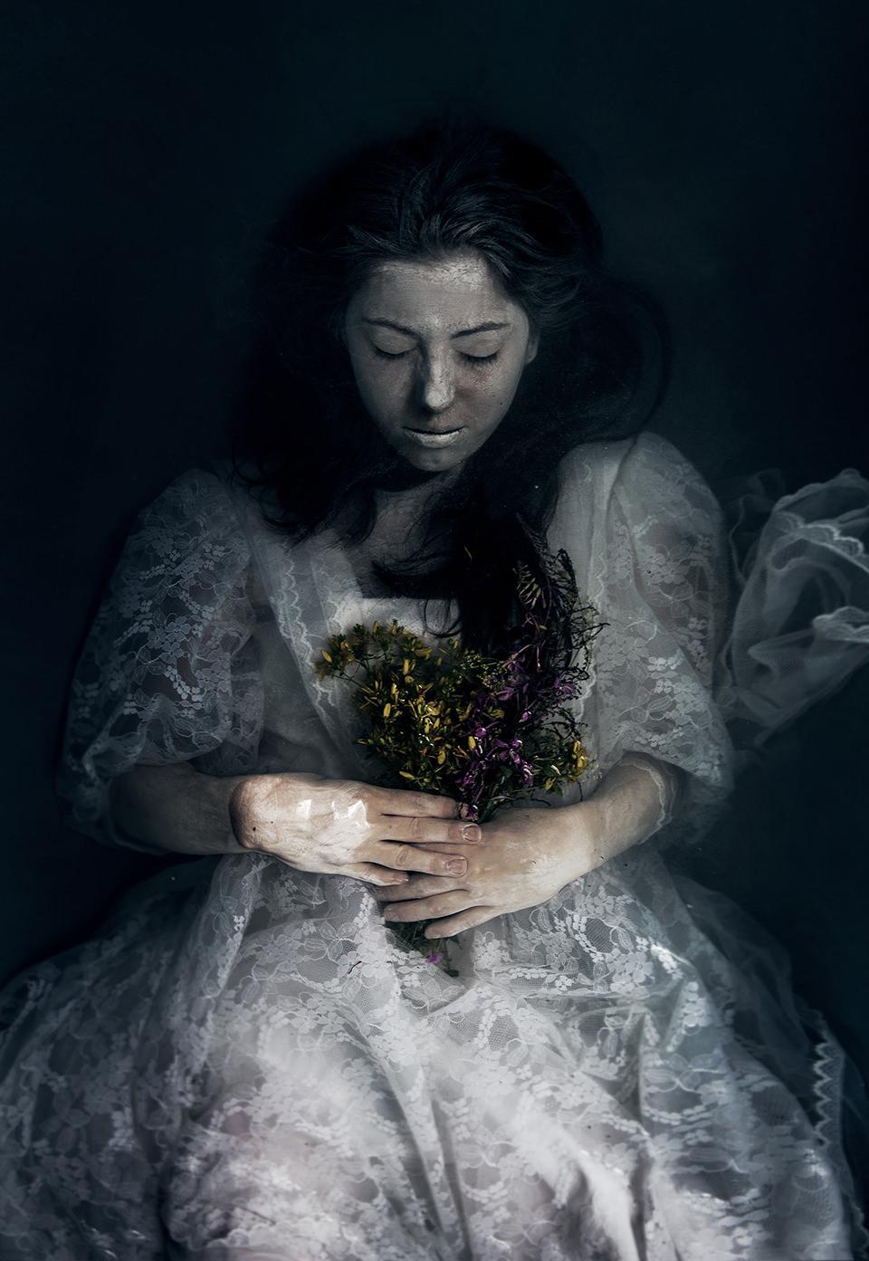 Eine Frau mit weißem Gesicht und Blumenstrauß in der Hand unter dem Wasser.