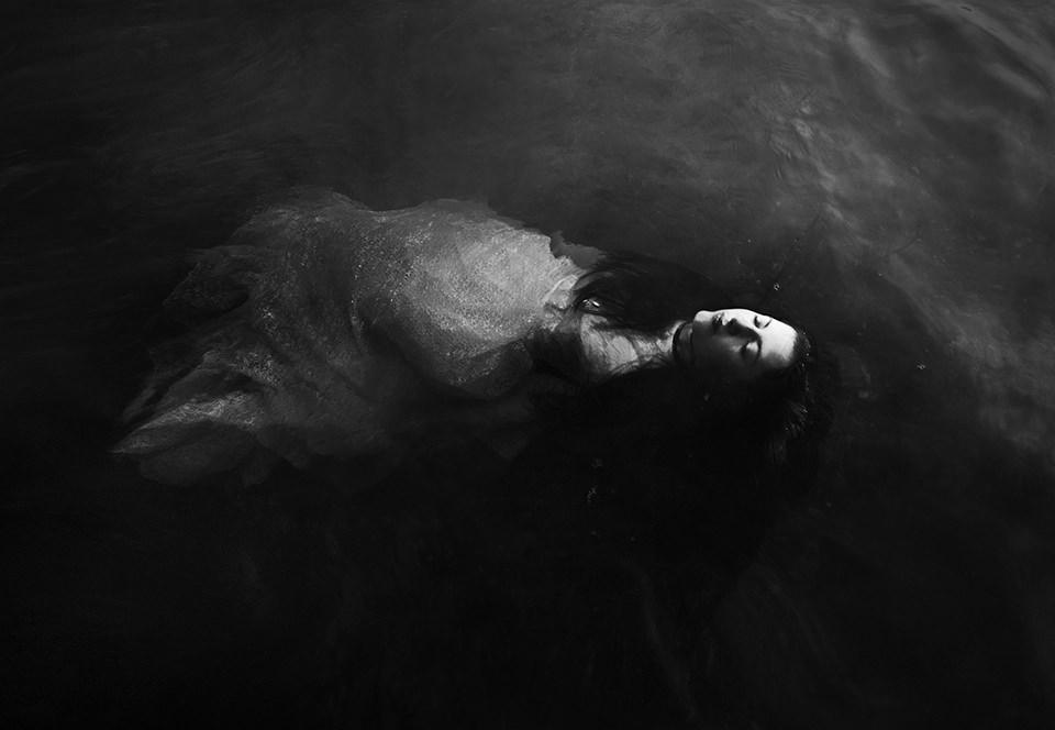 Eine Frau im Kleid treibt auf dem Wasser.
