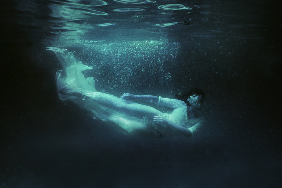 Eine Frau im weißen Kleid taucht seitlich Unterwasser.