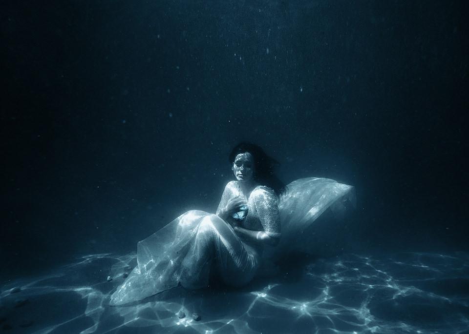 Eine Frau sitzt auf dem Grund eines Gewässers und umklammert einen Stein.