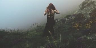 Eine Frau in schwarzem Kleid geht im Nebel eine Böschung mit Blumen hinunter.