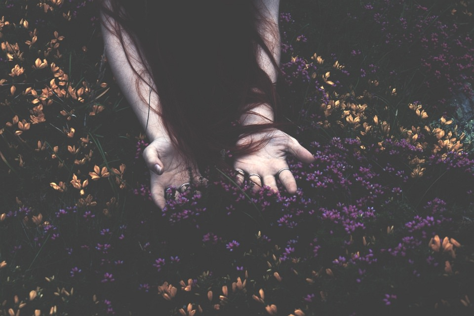 Von langen Haaren umspielte Hände legen sich in viele kleine Blüten.