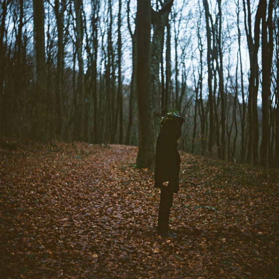 Eine Person mit Efeu auf dem Kopf steht im Wald.