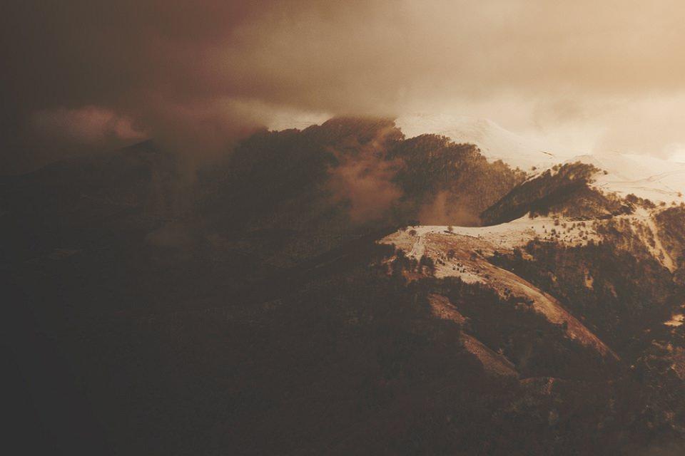 Bewaldete Berge in tiefhängenden Wolken.
