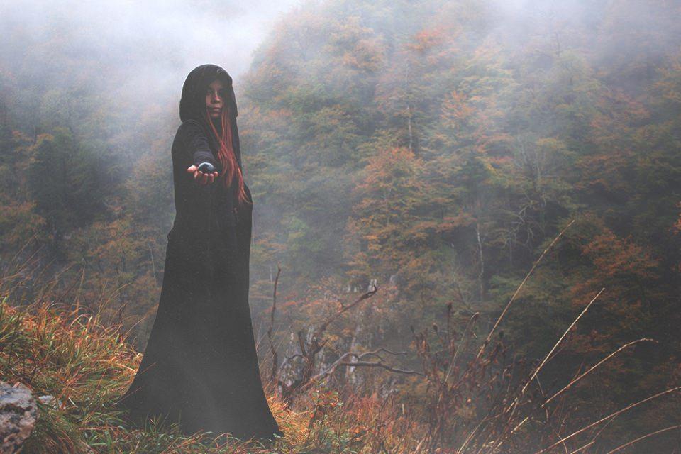 Ein Mädchen mit Umhang und Kapuze hält eine Glaskugel in der ausgestreckten Hand vor einem herbstlichen Wald.