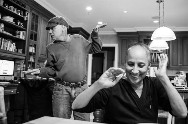 Eine Frau im Vordergrund lacht und ein Mann im Hintergrund macht eine lustige Verrenkung.