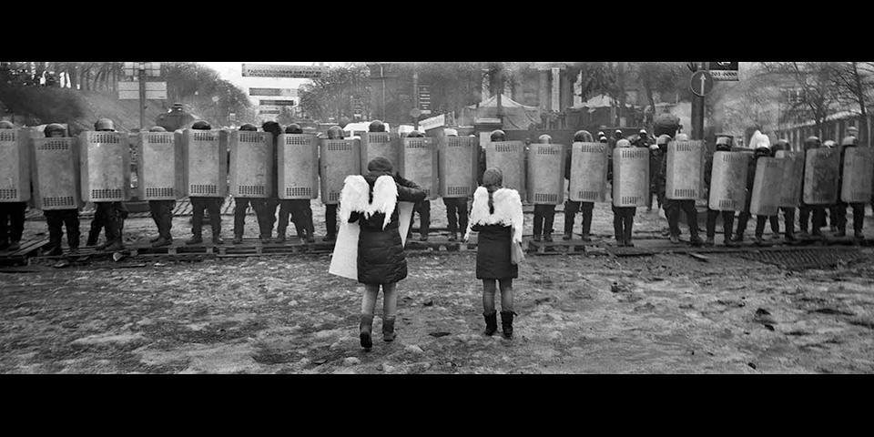 Kinder mit Engelsflügeln vor Polizeiabsperrung