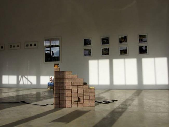 Ein Raum mit Bildern und aufgeschichteten Bausteinen.