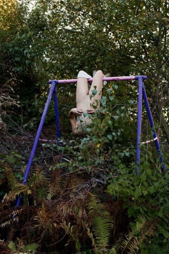 Eine Frau hängt kopfüber von einem Kindergerüst.