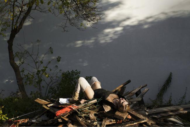 Eine Frau liegt vor einer Wand. Die Sonne erleuchtet ihren Körper.