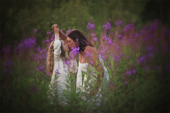Mutter und Tochter zwischen violetten Blumen geben sich einen Kuss.
