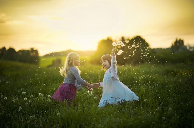 Zwei Mädchen tanzen auf einer Wiese mit einem Strauß Pusteblumen.