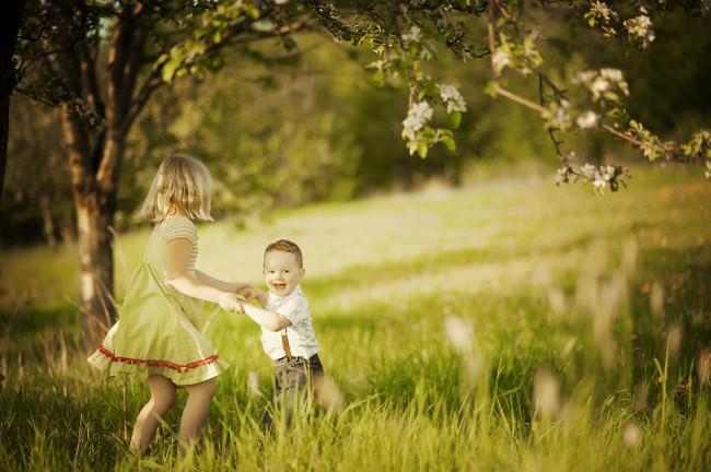 Ein Mädchen und ein Junge tanzen auf einer Wiese.