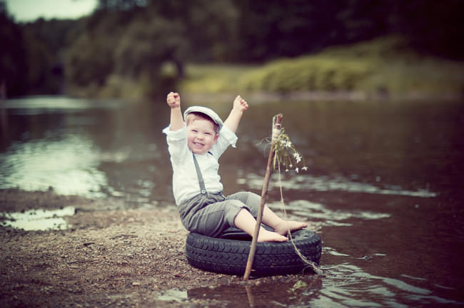 Ein Junge auf einem Reifen an einem kleinen Fluss.
