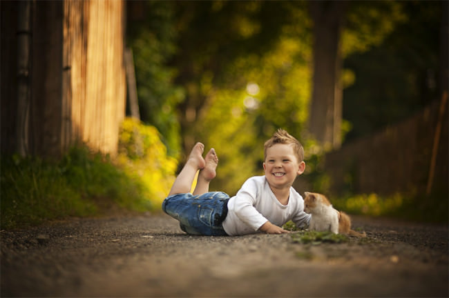 Eine Junge liegt mit einer Katze zusammen auf einem kleinen Weg und lacht.