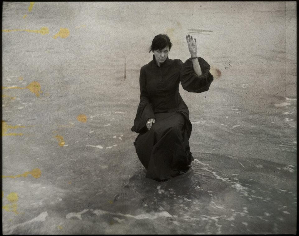 Eine Frau sitzt im Wasser und hebt ihren Arm.