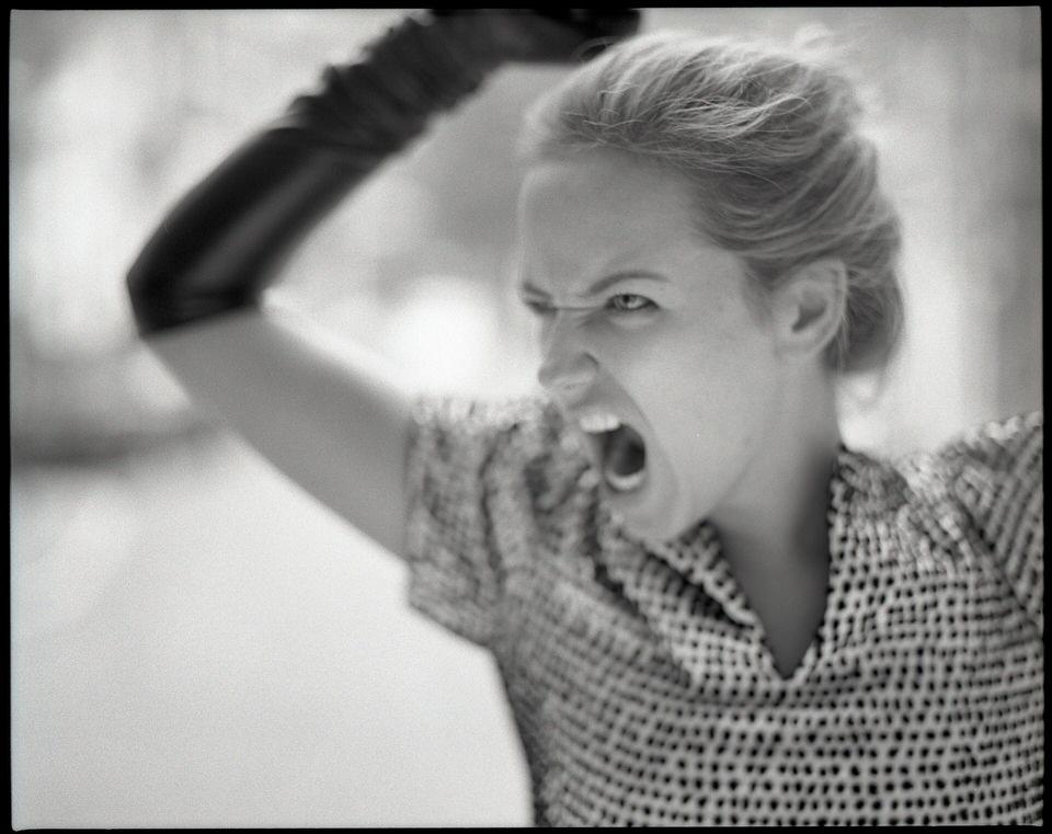 Eine Frau schreit voller Wut.