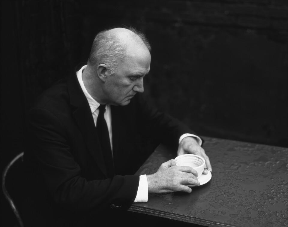 Ein alter Mann am Tisch mit Kaffeetasse.