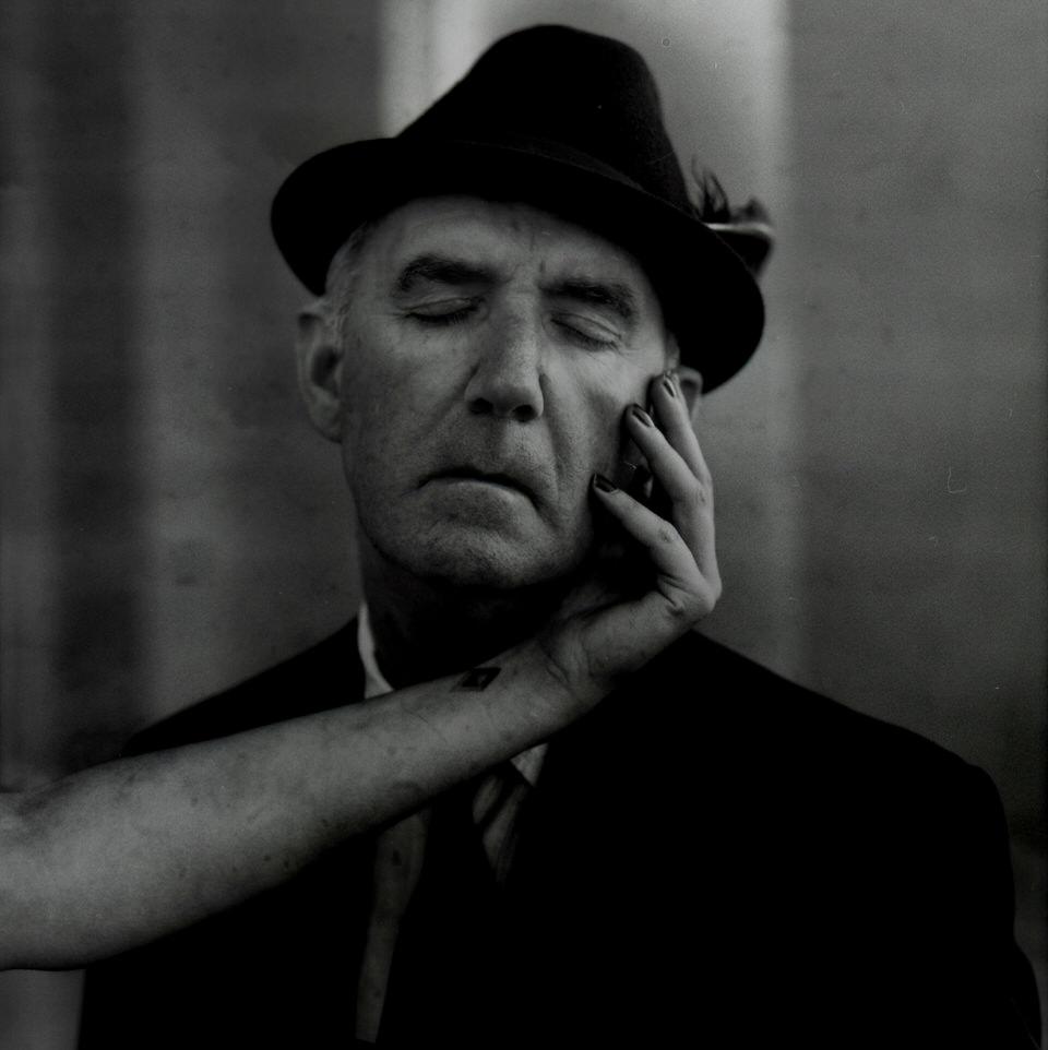 Ein älterer Mann mit geschlossenen Augen. Ein Arm streichelt seine Wange.
