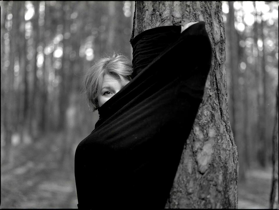 Eine Frau hält Stoff nach oben, so dass man nur einen Teil ihres Gesichts sieht.