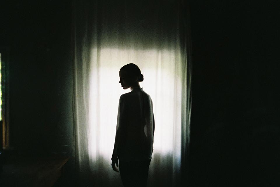 Eine Frau steht im Gegenlicht vor einem Vorhang.