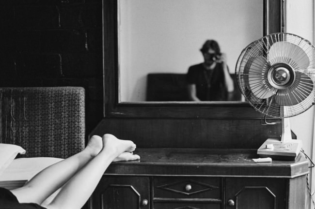 Der Fotograf fotografiert sich im Spiegel. Die Füße seiner Freundin sind sichtbar.