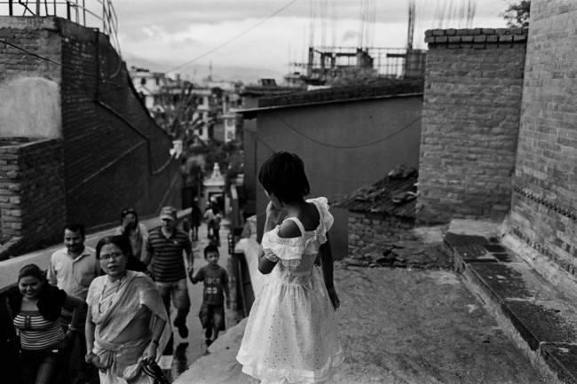 Ein Mädchen in einem weißen Kleid schaut auf die Straße.