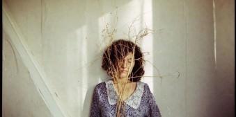 Frau steht an einer Wand mit Ast vorm Gesicht