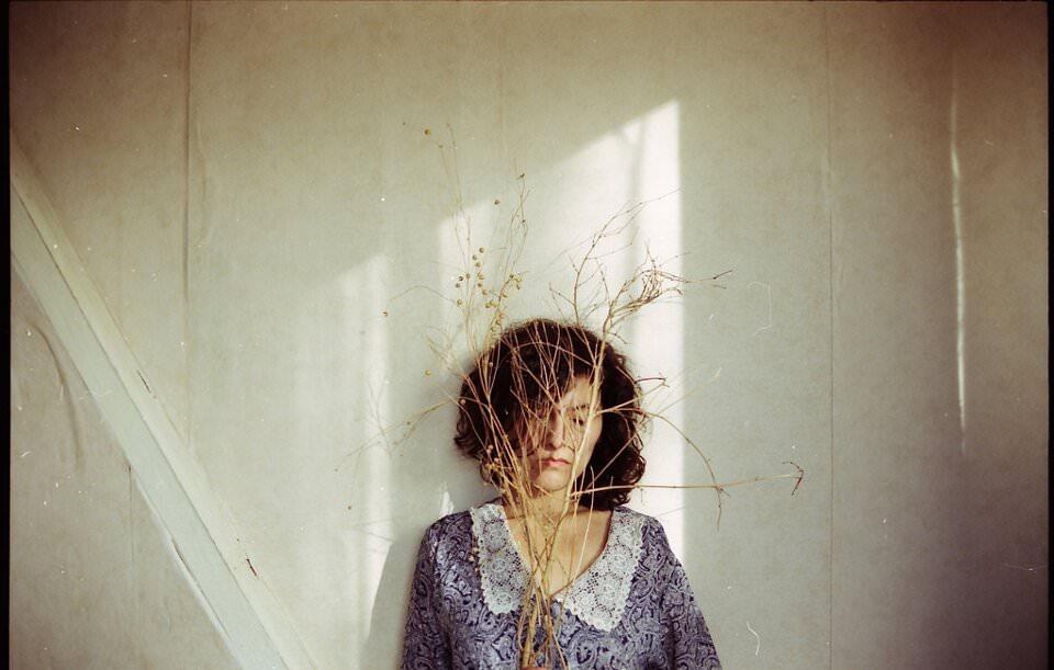 Eine Frau steht an einer Wand mit einem Ast vorm Gesicht