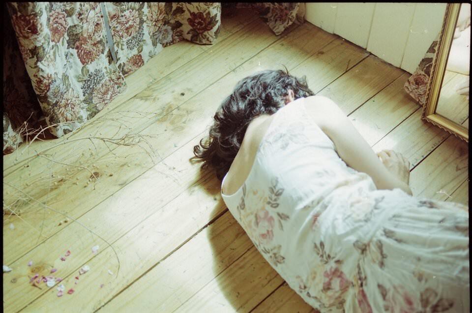 Frau liegt auf Holzboden