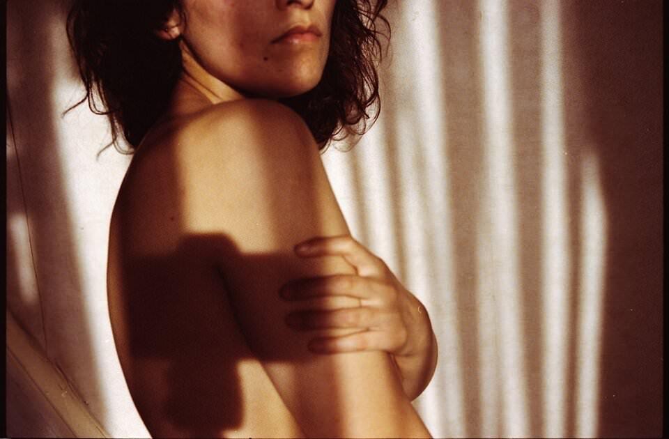 Halbnackte Frau umfasst ihren Körper