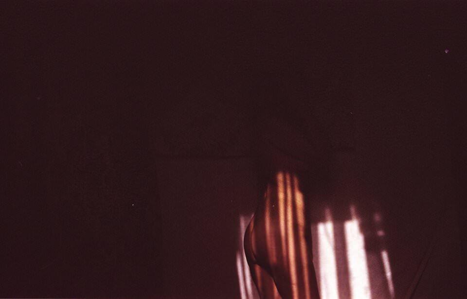 Frau lehnt nackt an einer Wand mit wenig Lichteinfall